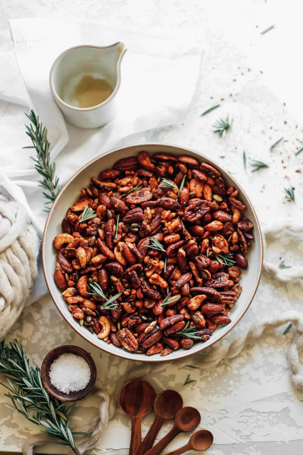 A large bowl of Sweet and Smoky Mixed Holiday Nuts with rosemary sprigs.