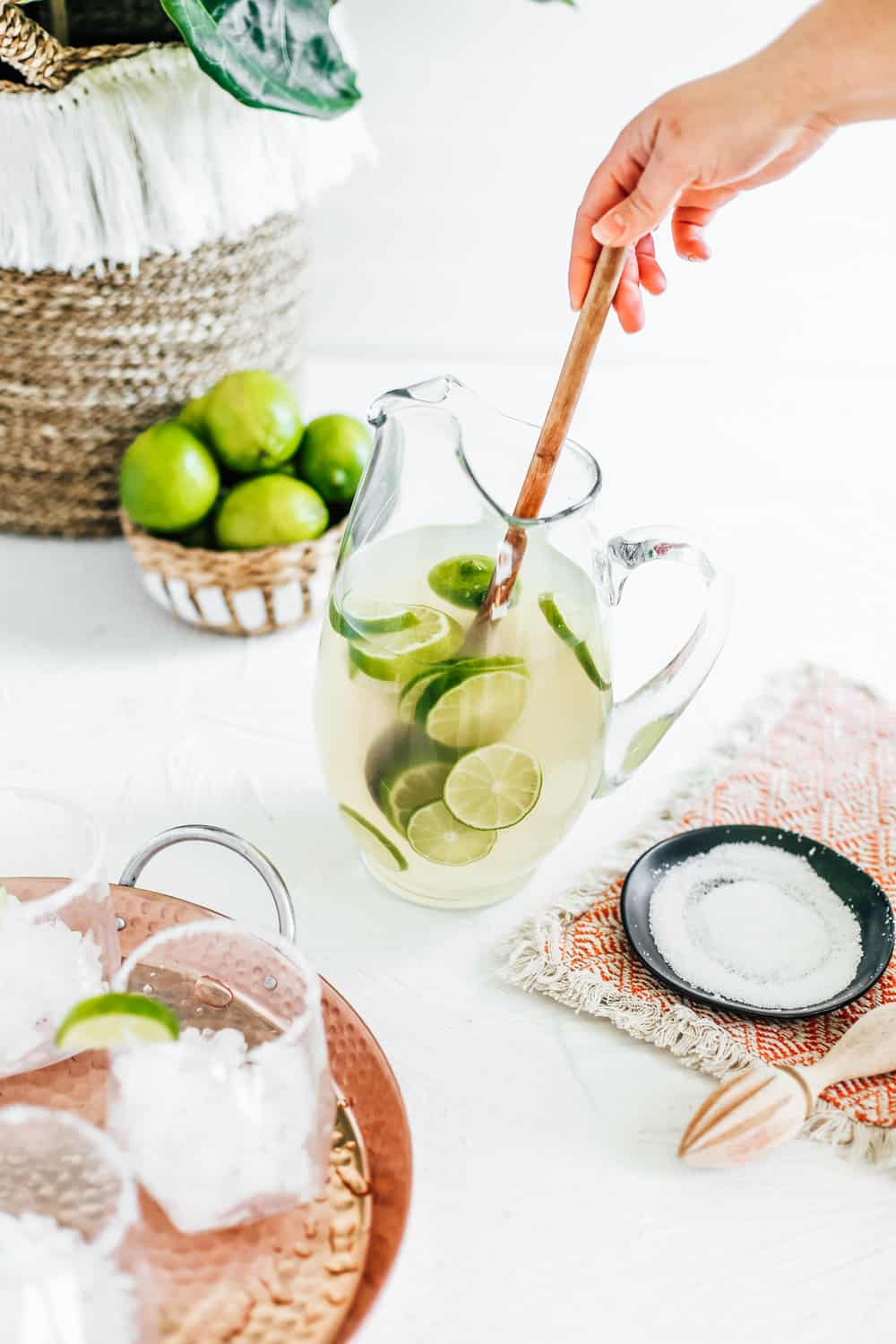 A pitcher filled with a classic margarita with limes and a wooden spoon.