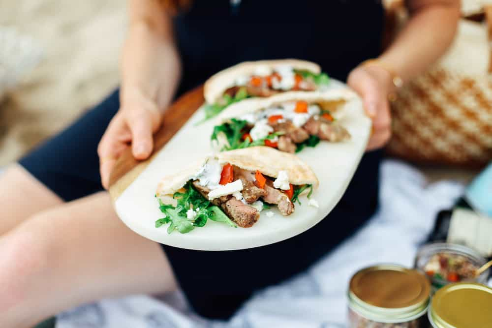 Elizabeth holding Garlic Lamb Pita Pockets with Summer Herb Slaw on a white serving board