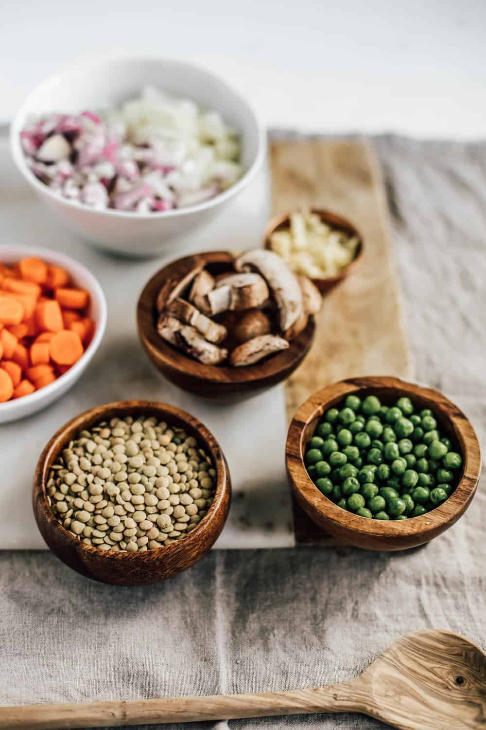 Small wooden bowls of peas, lentils, carrots, mushrooms, and diced onion.