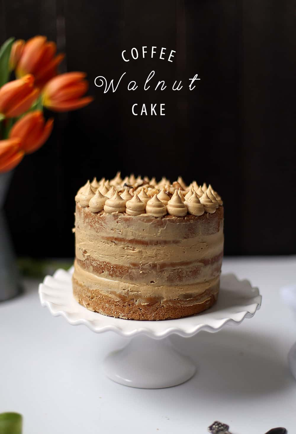 Three layer Coffee Walnut Cake on a white cake stand.