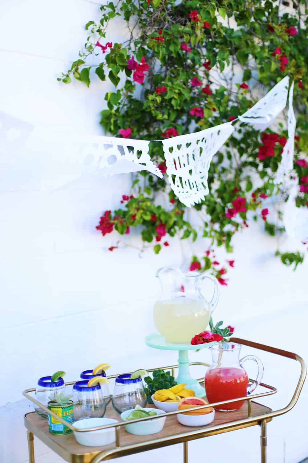 DIY Margarita Bar with juice in pitchers and margarita glasses on a bar cart