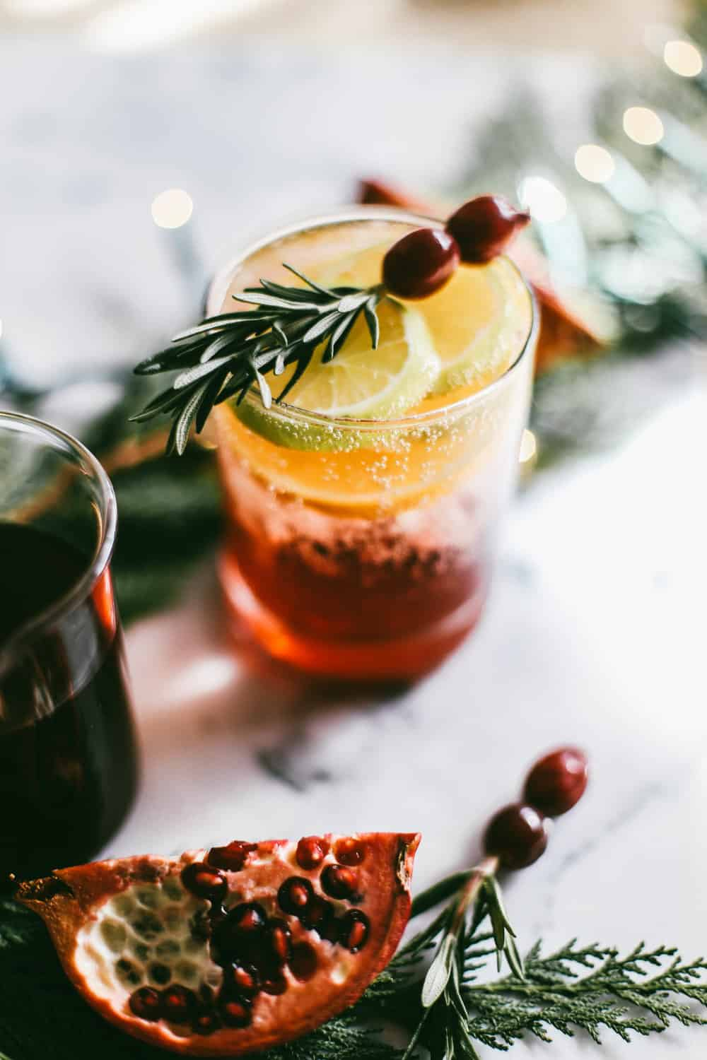 Low glass filled with pomegranate juice and champagne garnished with orange slices, rosemary and cranberries.