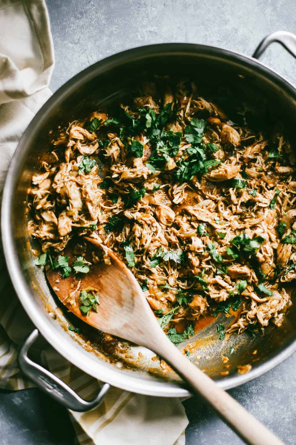 A pan with shredded chicken and cilantro being stirred with a wooden spoon.