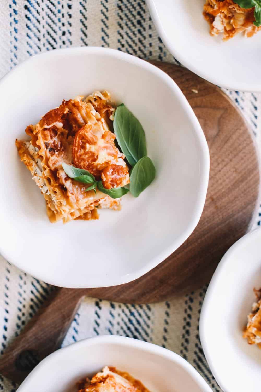 A serving of homemade lasagna in a white bowl.