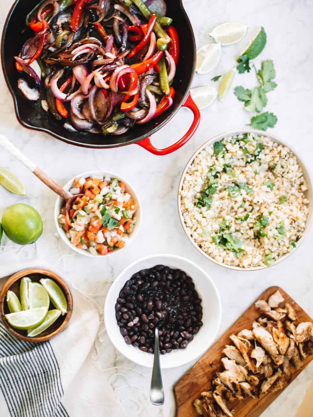 Chipotle style burrito bowls at home or for meal prep! These healthy bowls are made with cauliflower rice, juicy chicken, salsa and avocado crema!