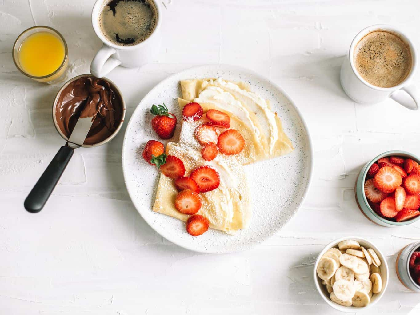 A plate of crepes with strawberries and sweet mascarpone filling