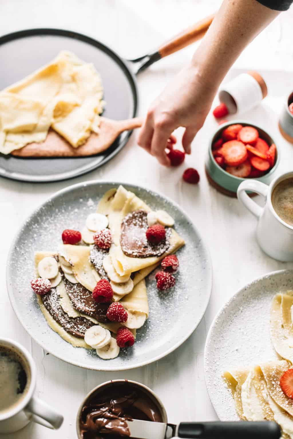 A plate full of crepes with sliced bananas, raspberries, and Nutella.