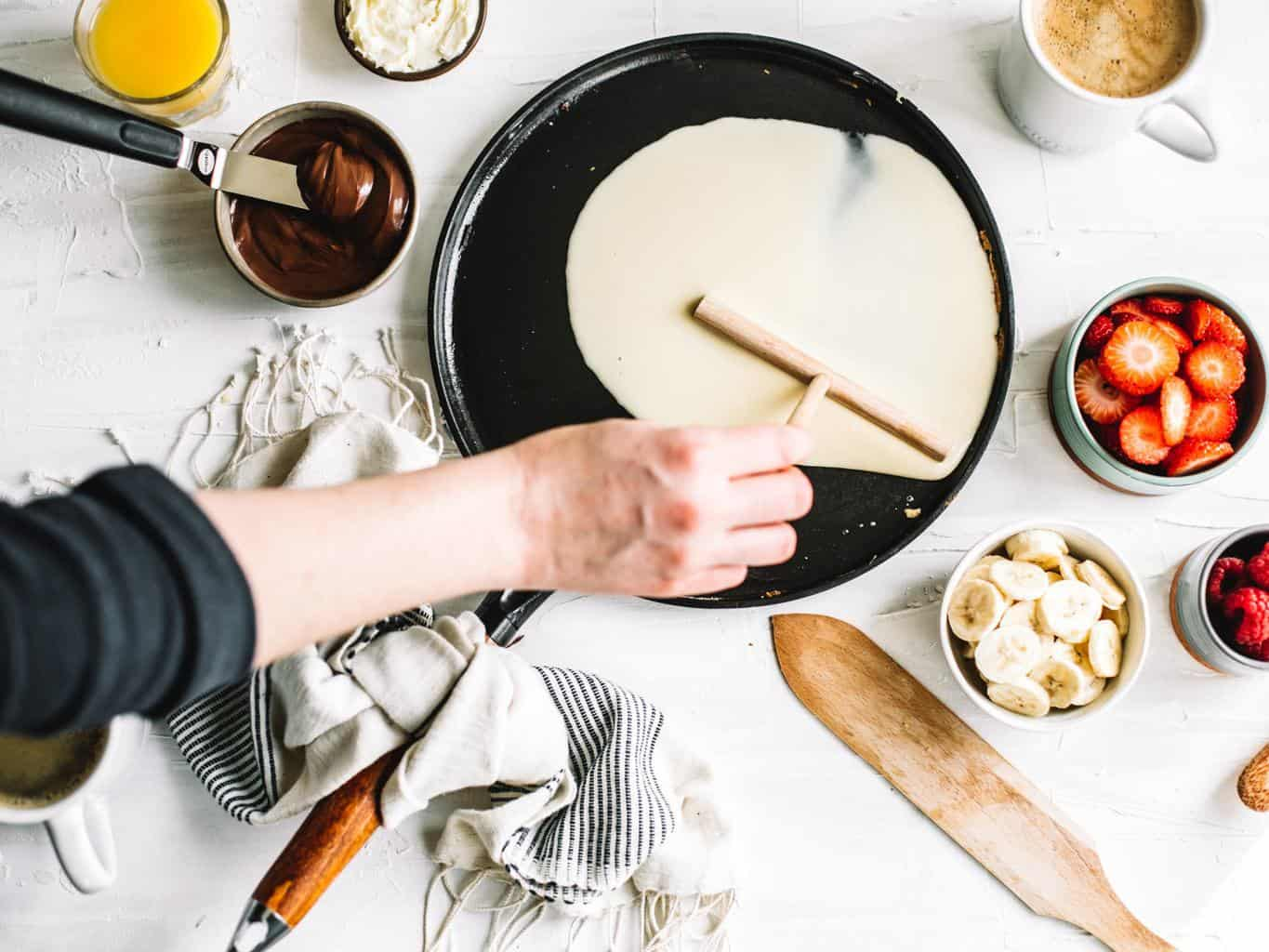 Crepe batter being spread out on a skillet.