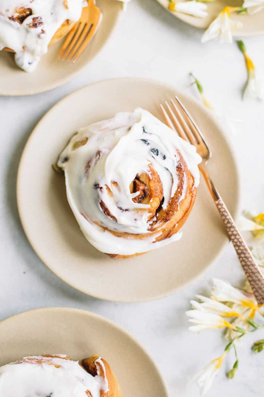 carrot cake cinnamon roll with cream cheese icing on beige plate with gold fork and flowers
