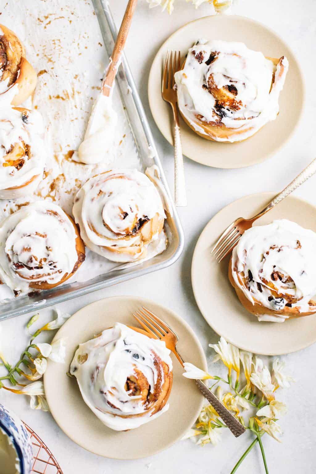 cream cheese glazed cinnamon buns on baking sheet and beige plates