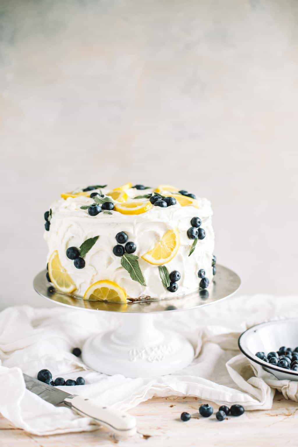 spring lemon blueberry cake with buttercream frosting on cake stand