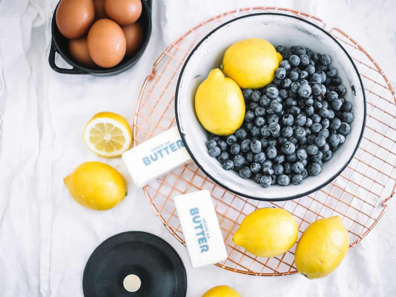 lemons and blueberries in white bowl, butter, lemons and eggs
