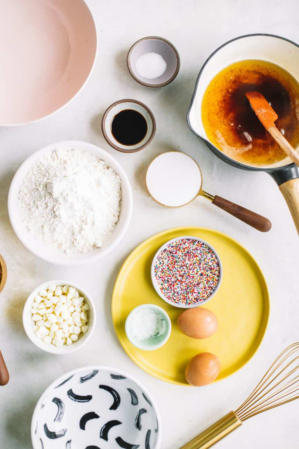 Ingredients for white chocolate sprinkle blondies in colorful bowls.
