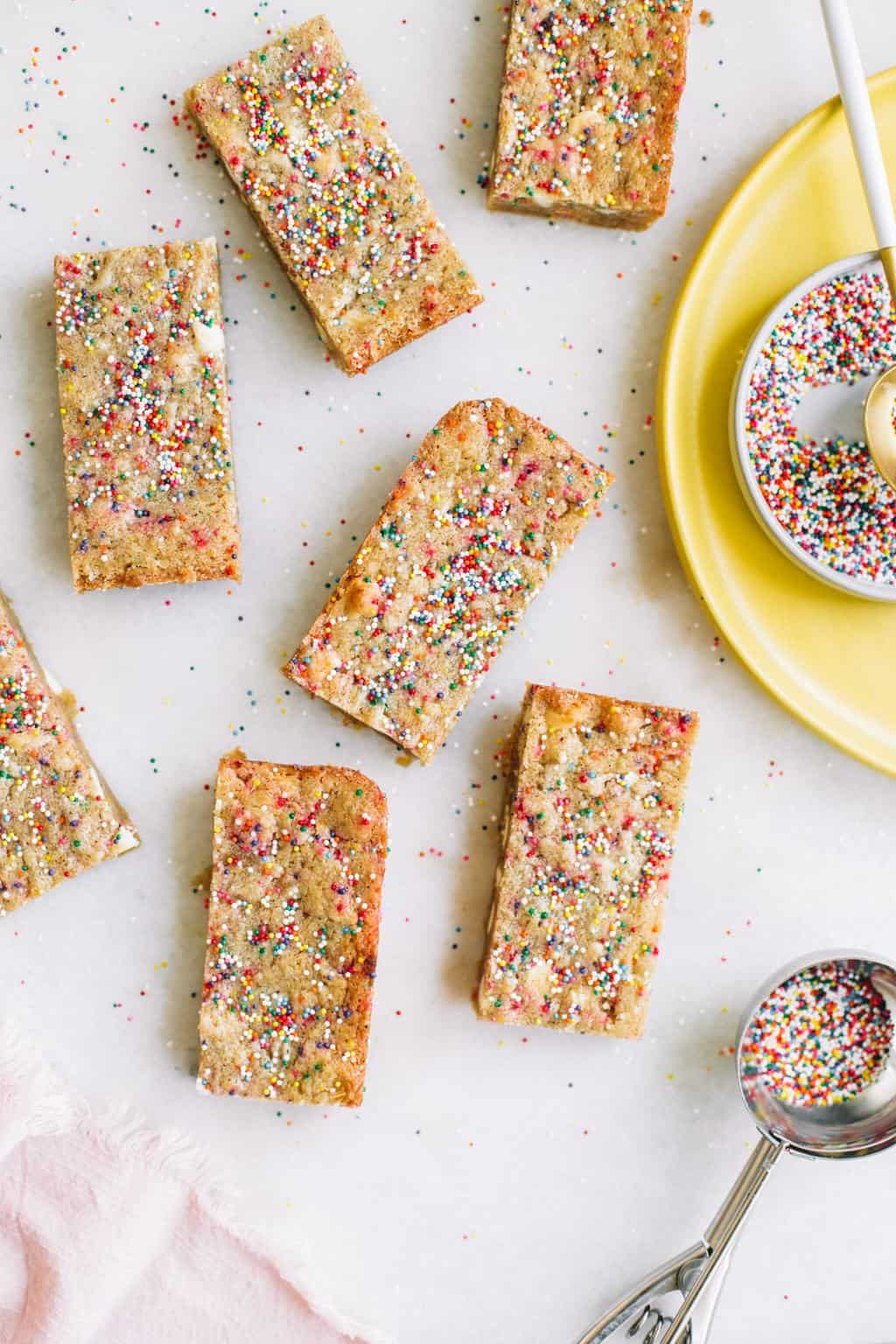 Blondies covered in sprinkles with a bowl of sprinkles.