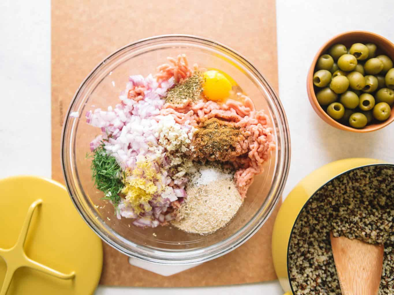 Ingredients for Greek meatballs in a clear bowl with quinoa in a yellow pot