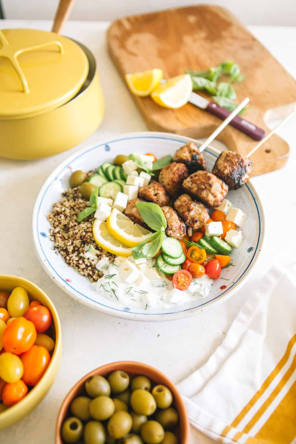 Mediterranean Greek Power Bowls in a white bowl with cherry tomatoes and yellow pot