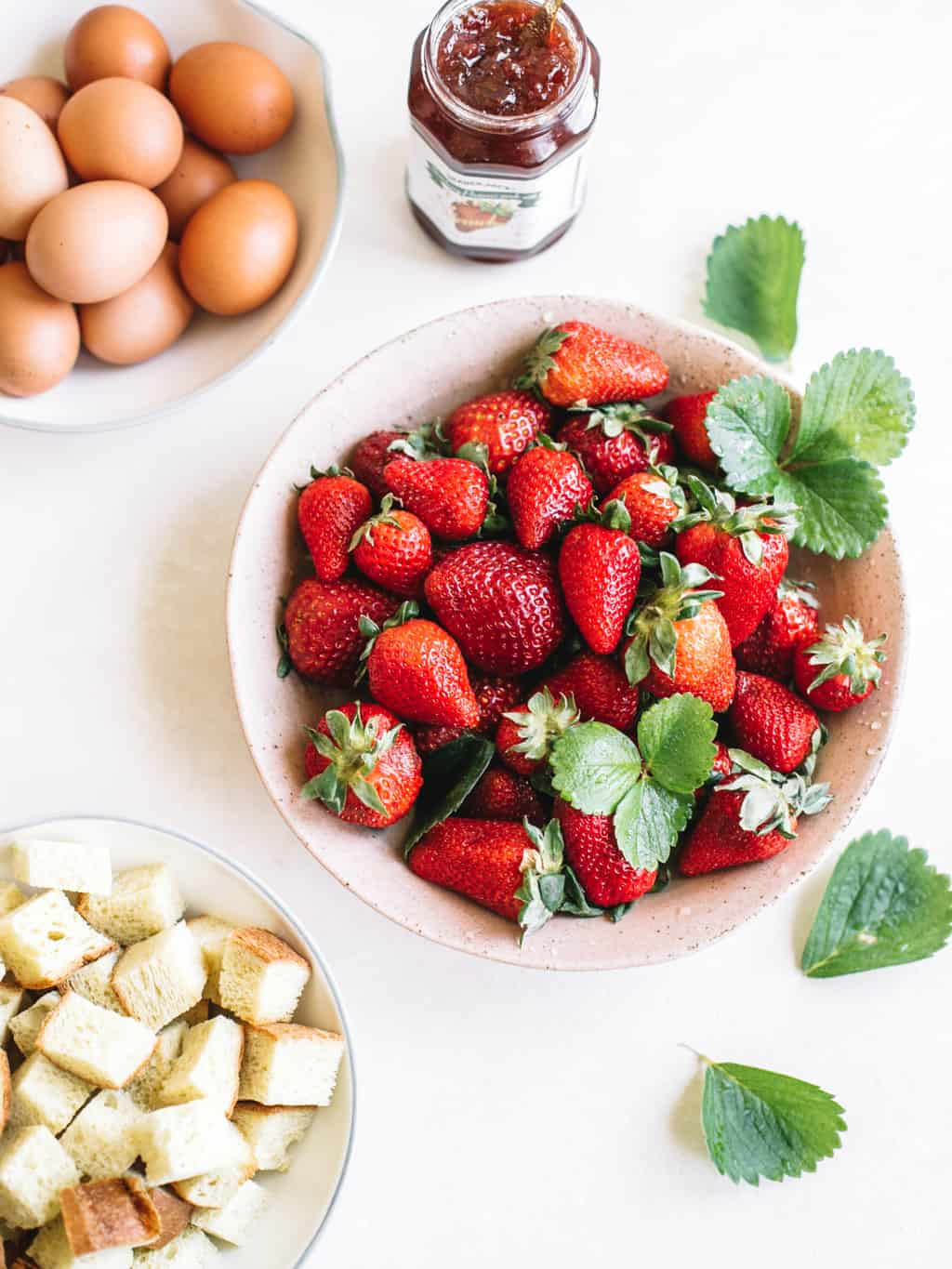 Fresh strawberries in a white bowl with bread cubes in a white bowl and eggs in a white bowl