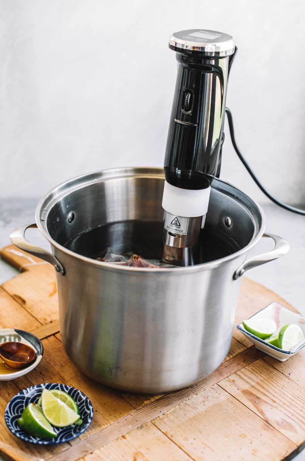 Sous vide machine inserted into large water bath in stainless steel pot
