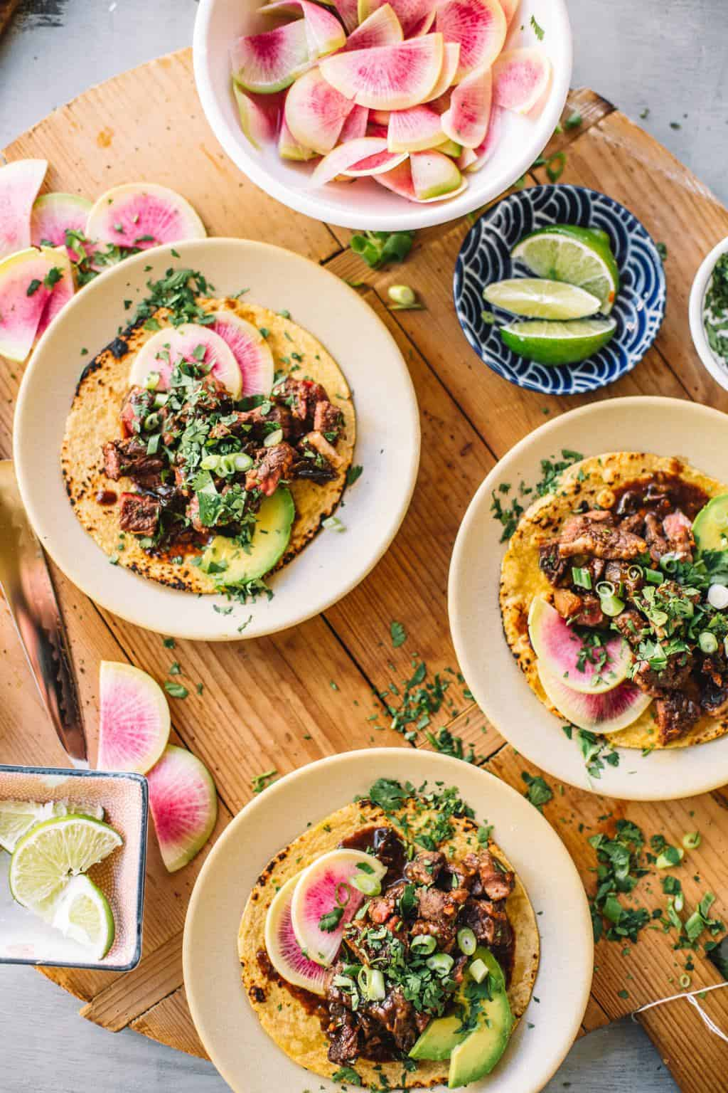 Three sous vide Asian short rib tacos on white plates with watermelon radishes and lime wedges in bowls