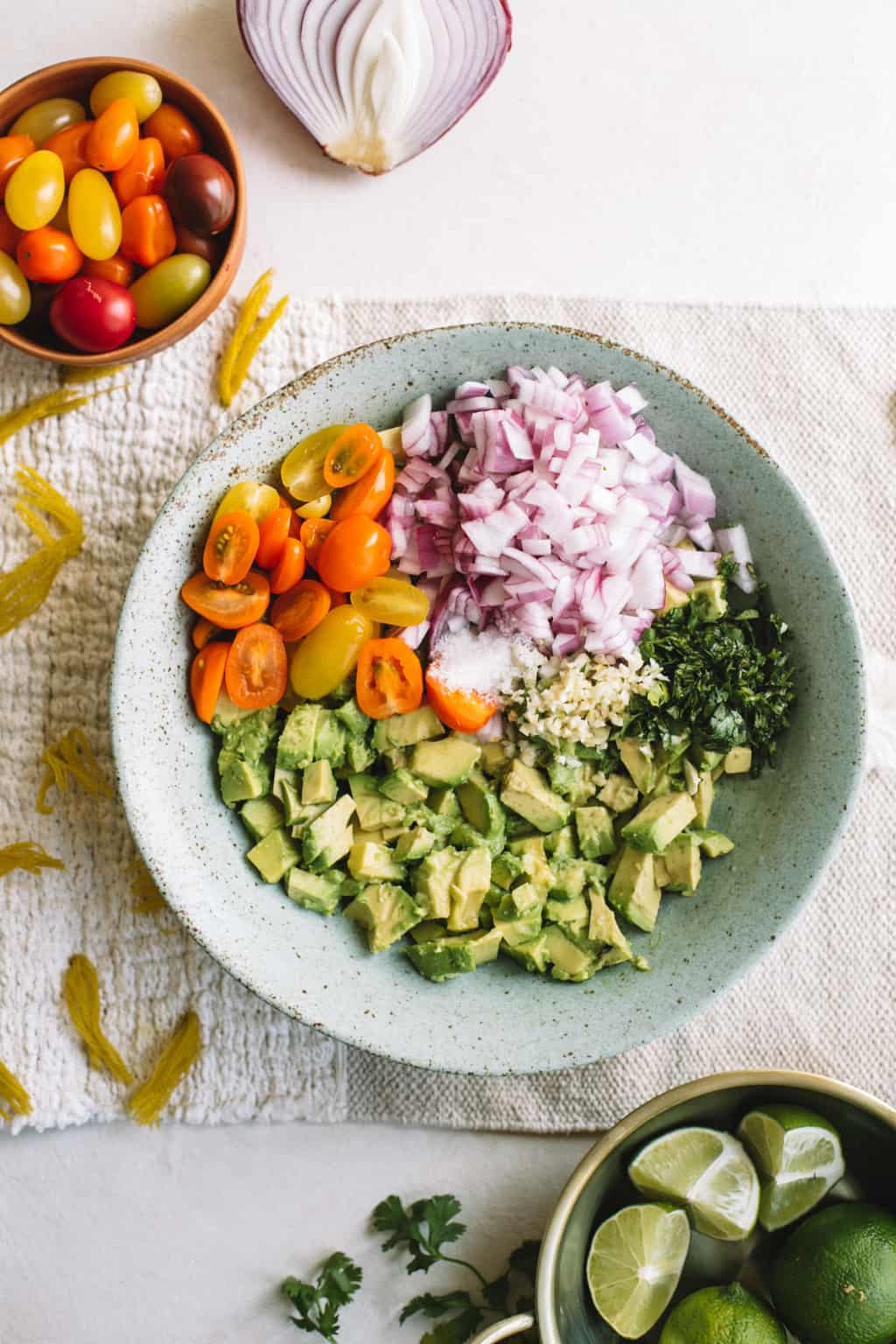 Blue bowl filled with avocado chunks, cilantro, red onion and heirloom cherry tomatoes.