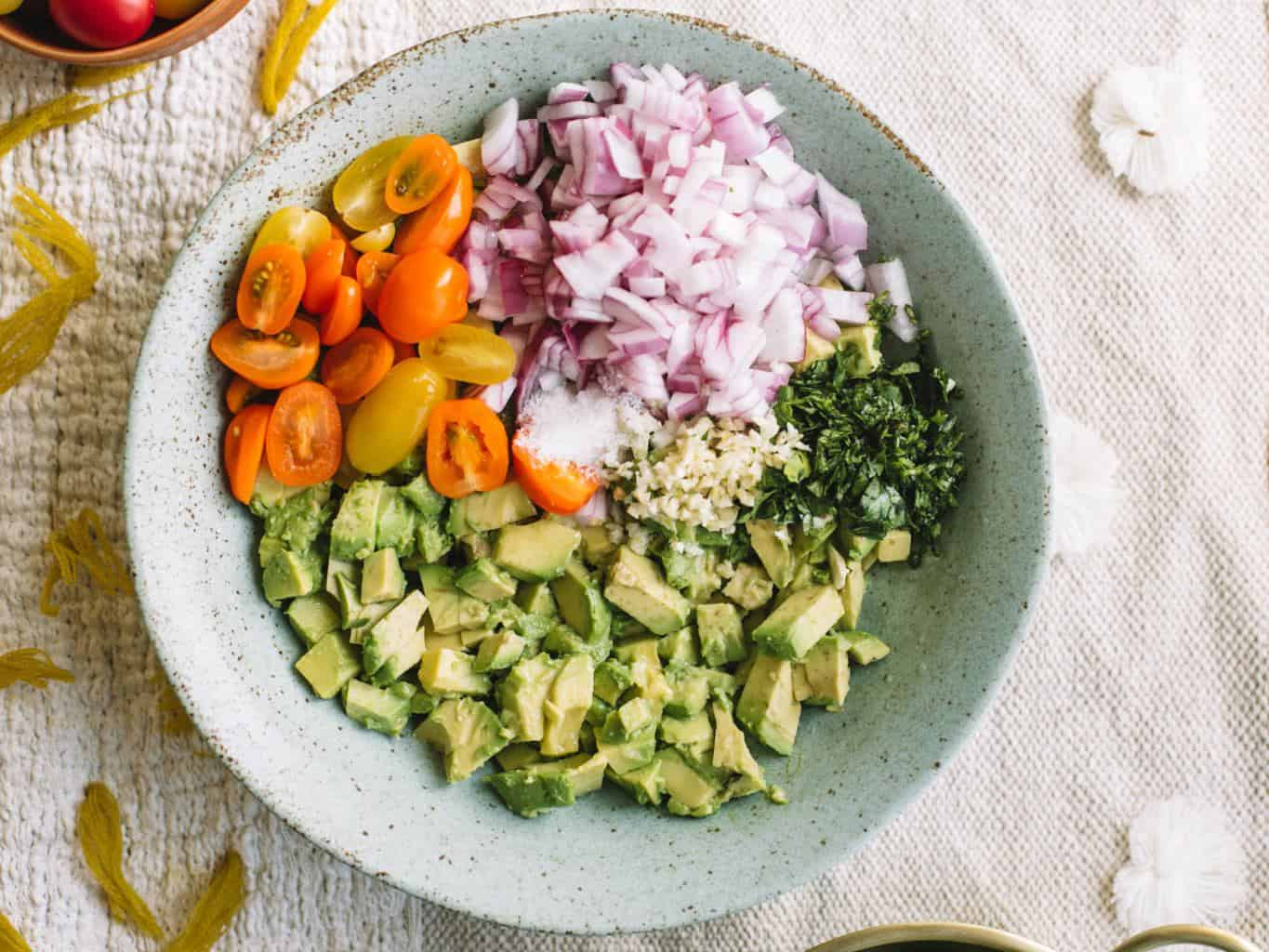Blue bowl filled with avocado, cilantro, garlic, red onions, and cherry heirloom tomatoes.