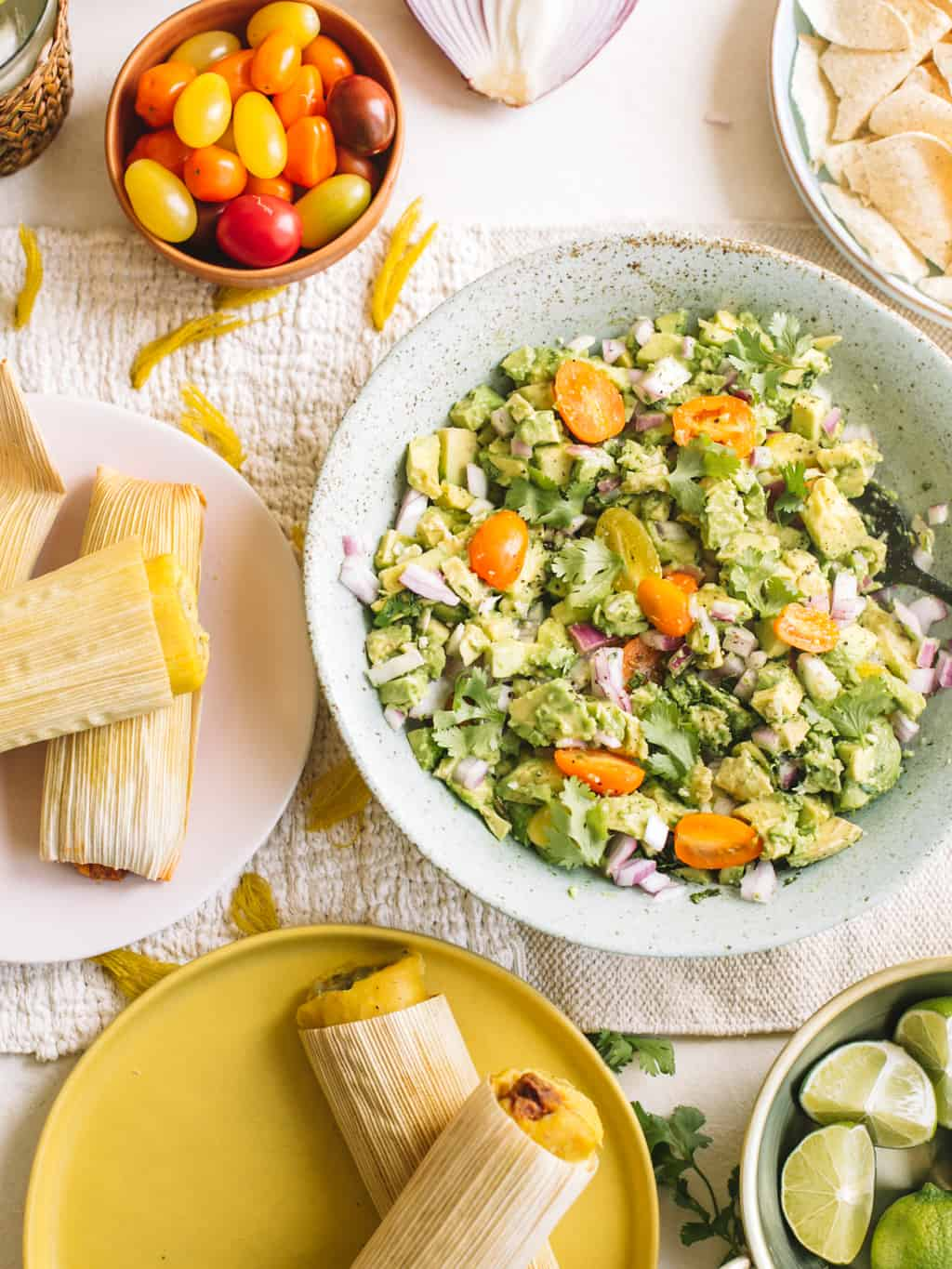 Blue bowl filled with deconstructed avocado salad and a side pink plate of tamales.
