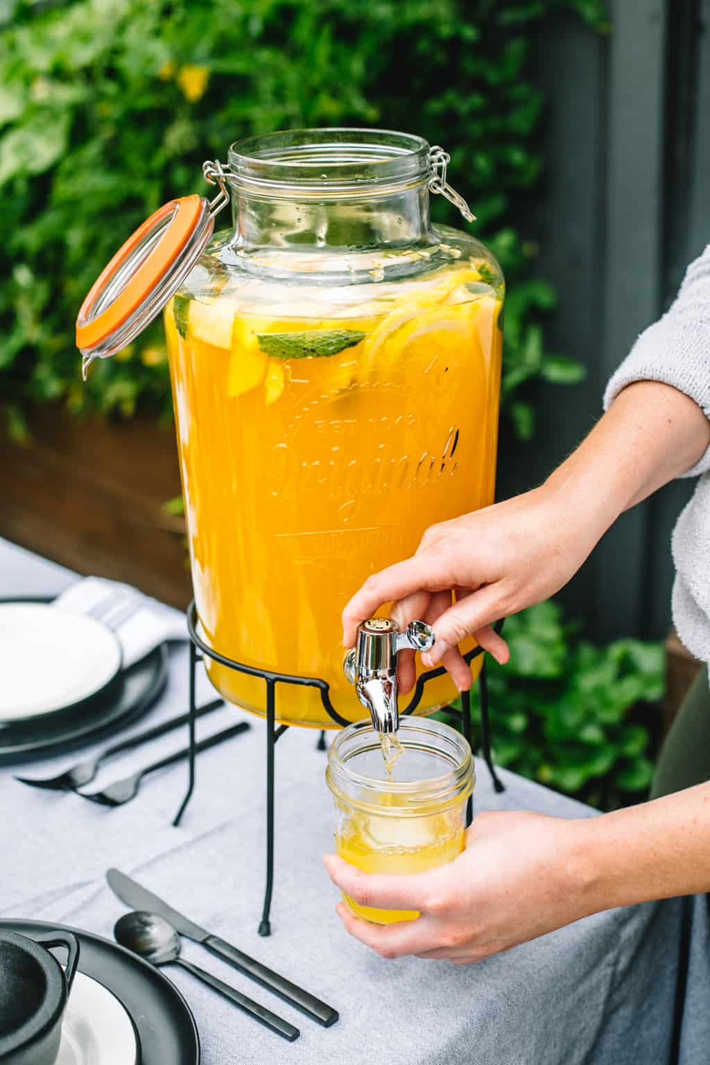 Beverage dispenser full of mango lemonade being poured into a mason jar.