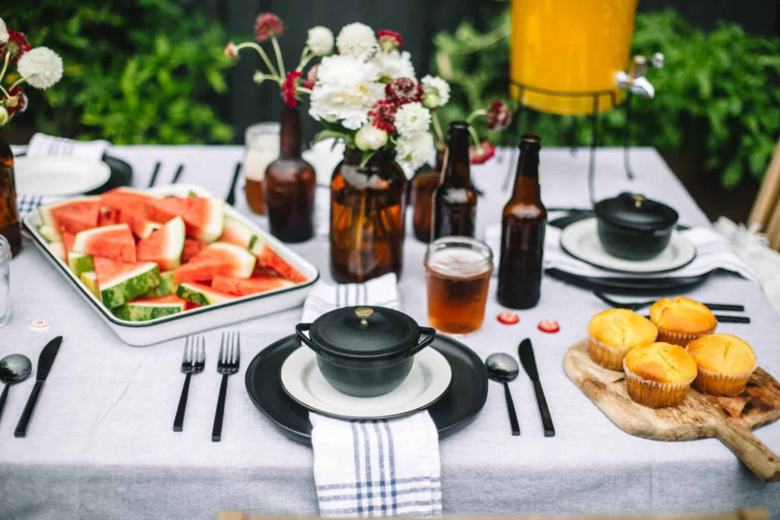Fathers day table set up with a platter of watermelon, cornbread and beer bottles.