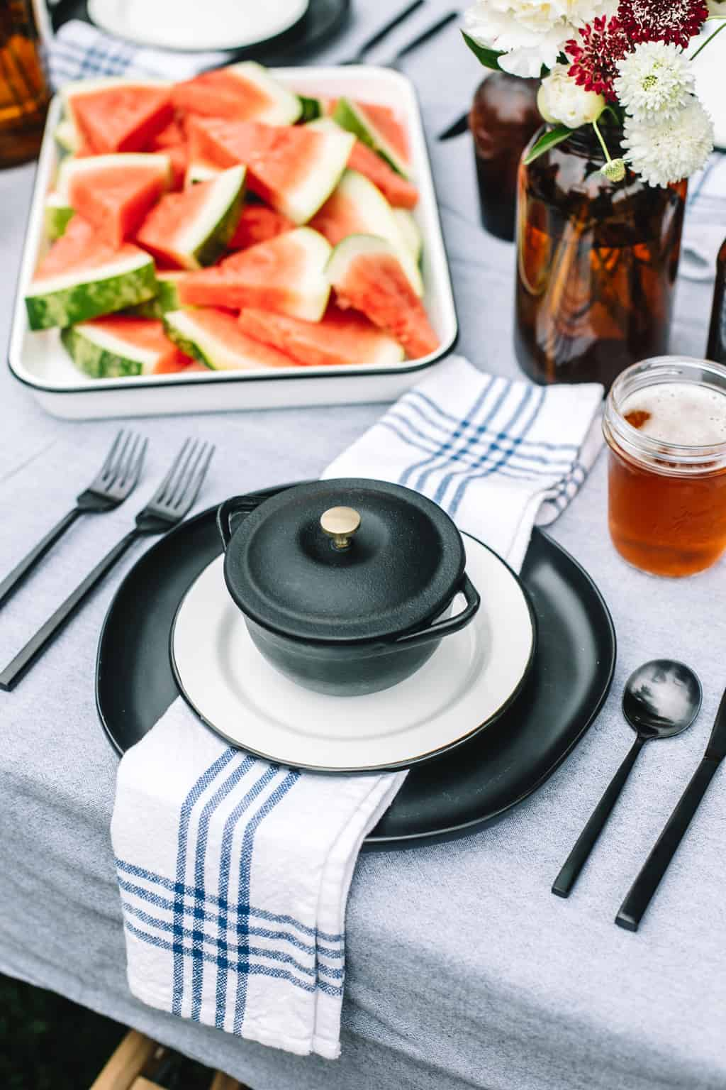 Black plate with a blue and white napkin and a platter of watermelon.