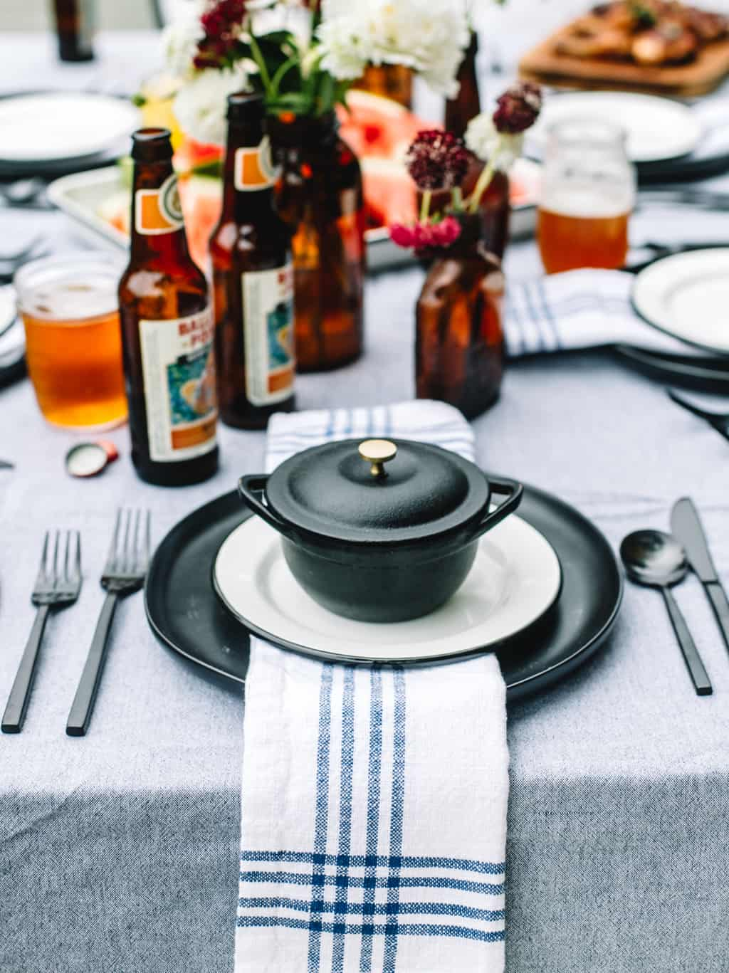 A black plate topped with a blue and white napkin on top of a tablescape.