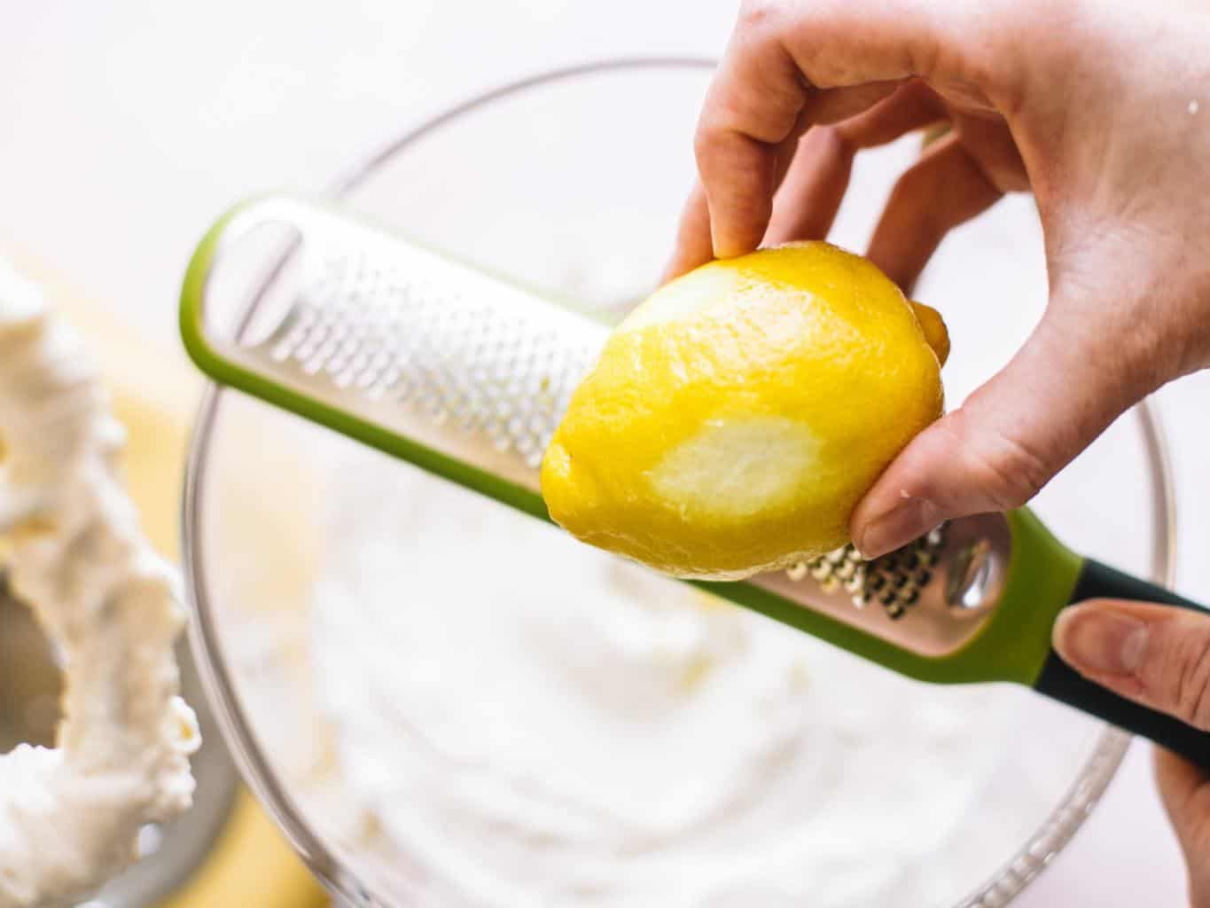 Lemon being zested over a clear bowl filled with whipped cream cheese