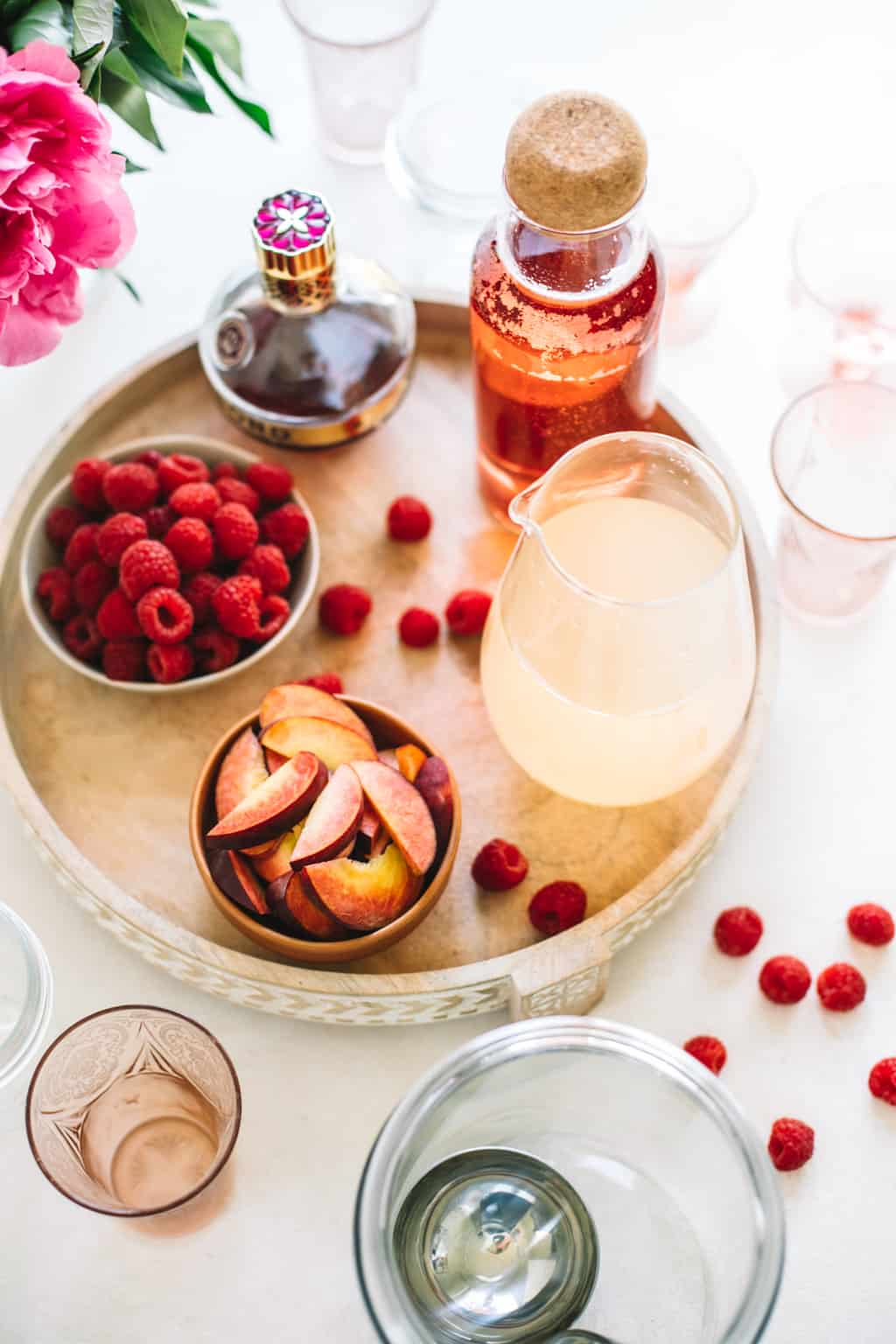 Fresh raspberries, fresh peach slices, lemonade in a pitcher, rosè in a pitcher and chambord on a wooden serving platter.