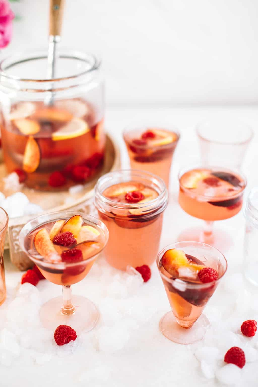 Rosè sangria with raspberries and peaches in cocktail glasses.