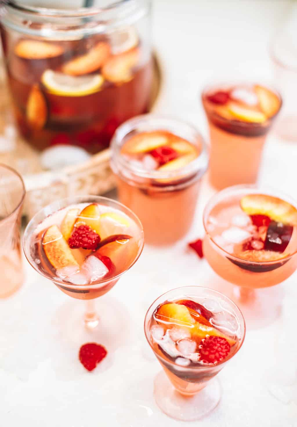 Rosè sangria with peaches and raspberries served in pink wine glasses.