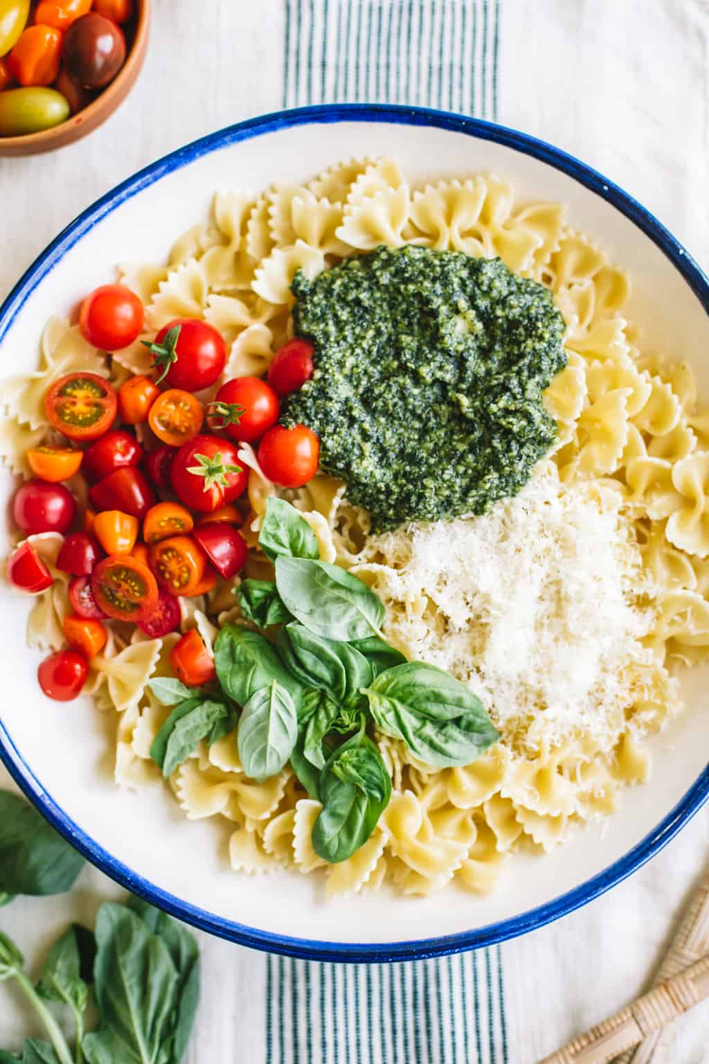 Pasta, pesto, tomatoes, Parmesan, and basil in a white bowl with blue rim