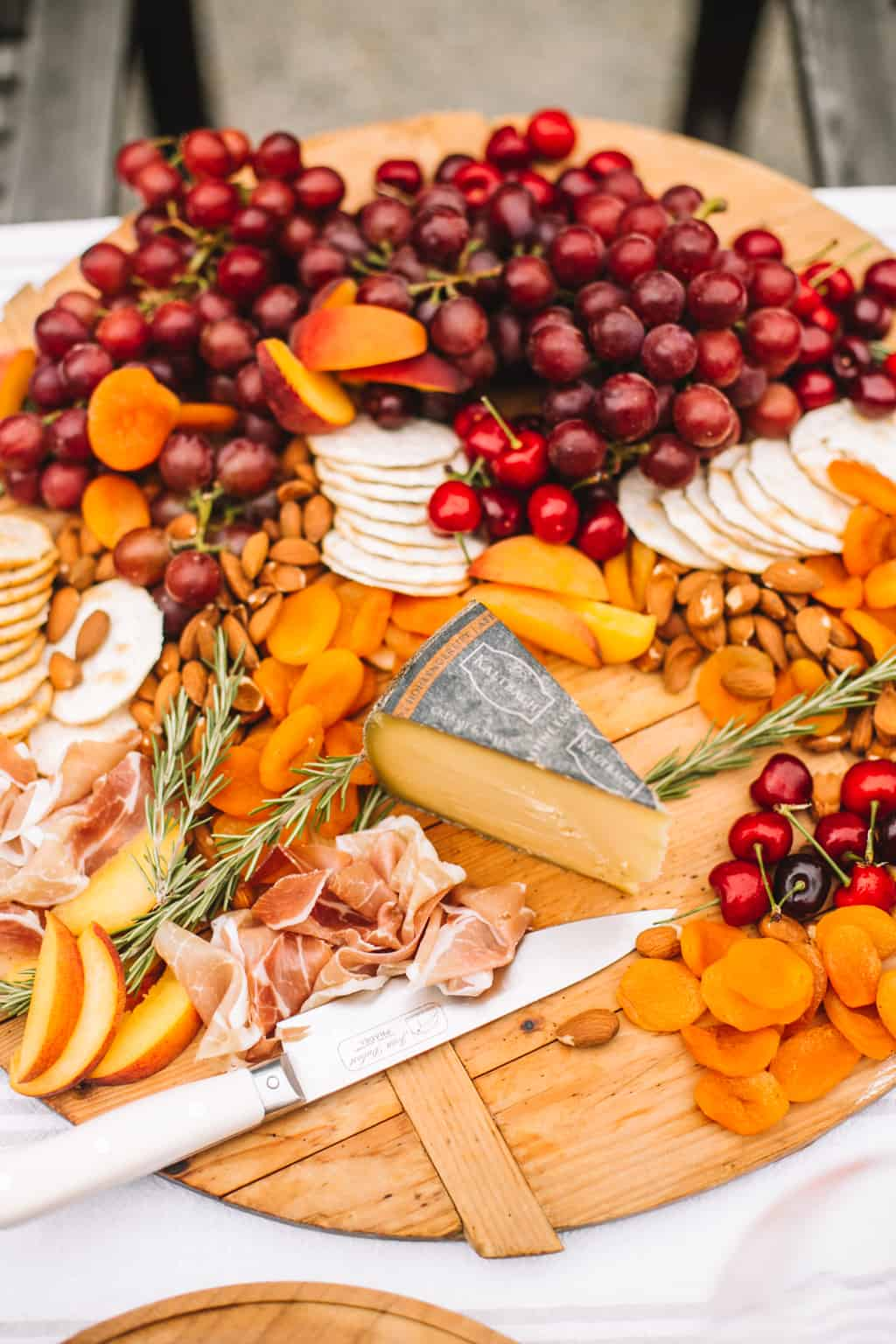 Wooden cheeseboard filled with dried apricots, cherries, grapes, crackers and a wedge of swiss cheese.