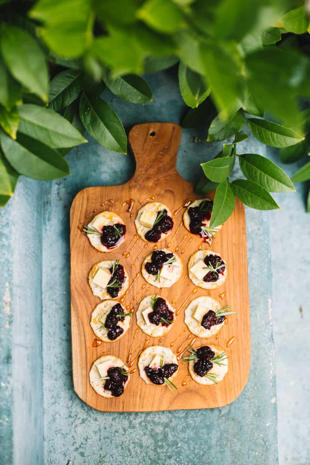 Wooden platter of cracker cheese appetizers with greenery.