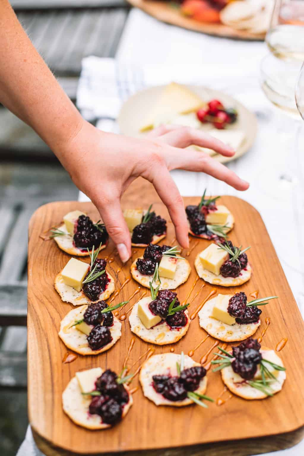 A wooden tray of cracker appetizers topped with swiss cheese and blackberry compote
