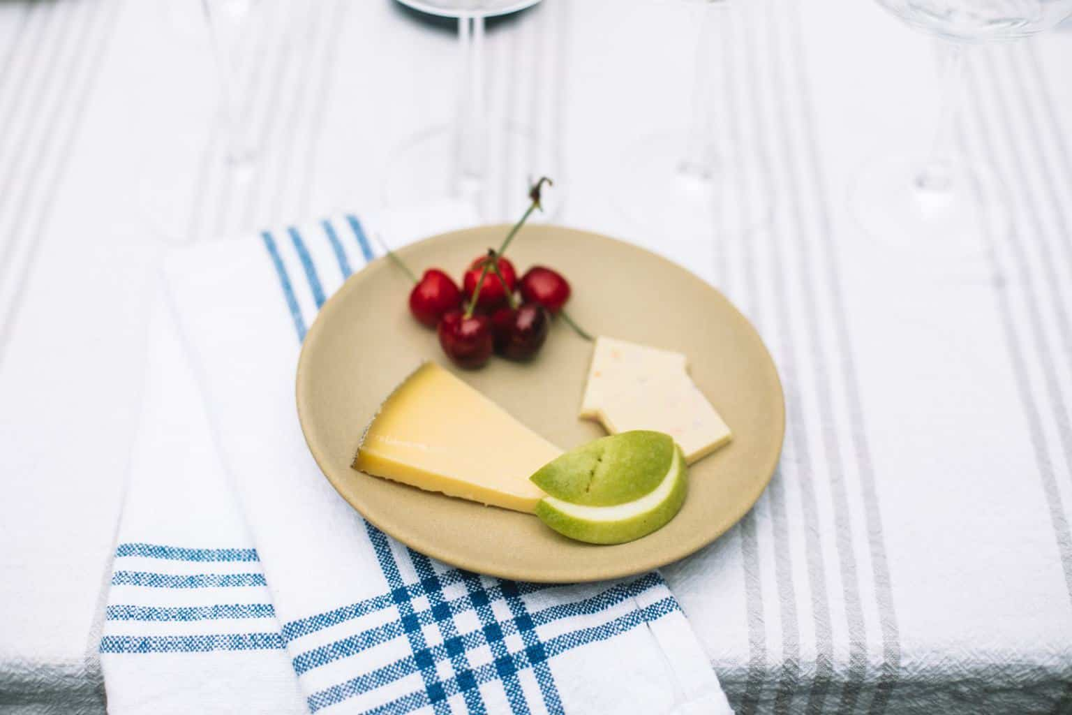 A small tan, ceramic tasting plate with cherries, cheese, apples and white chocolate.