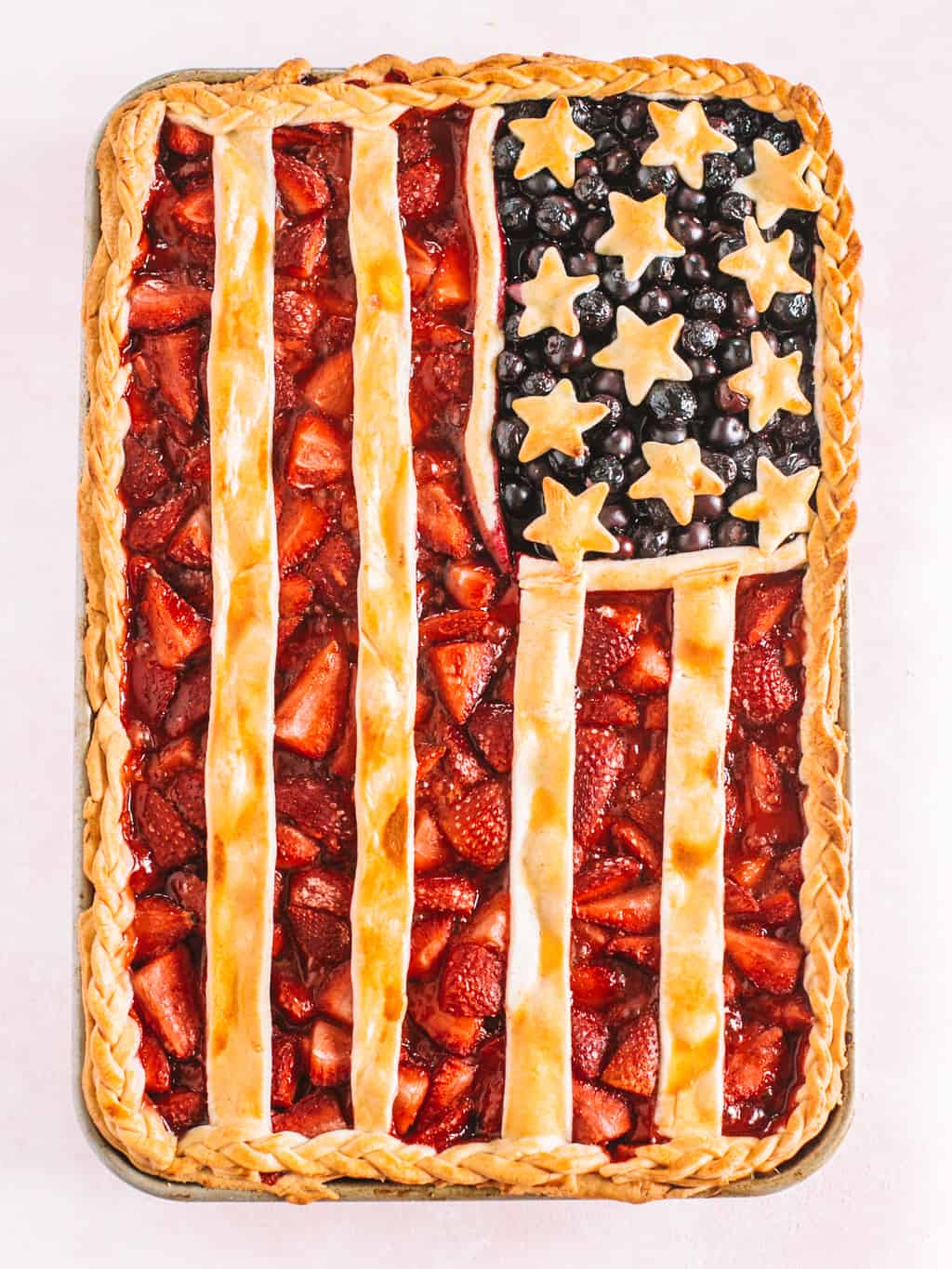 American flag pie baked on a baking sheet with a pink background.
