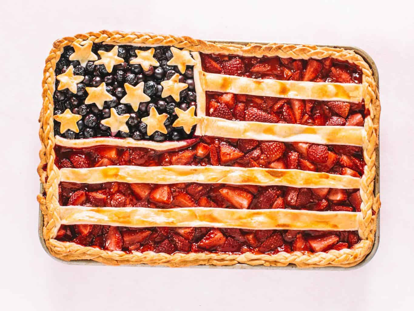 American flag pie made on a cookie sheet on a pink background.
