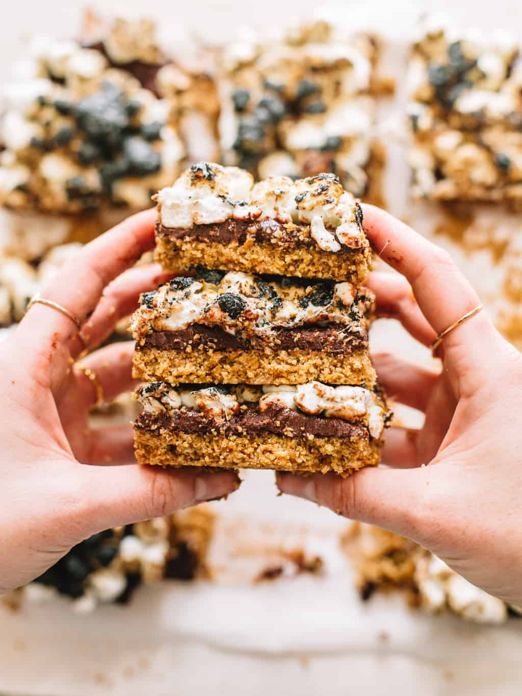Two hands holding a stack of smores bars.