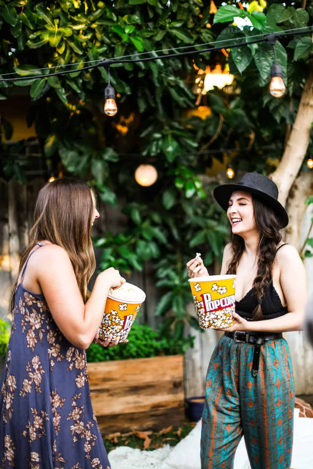 Two girls laughing throwing popcorn at each other at a backyard movie night.