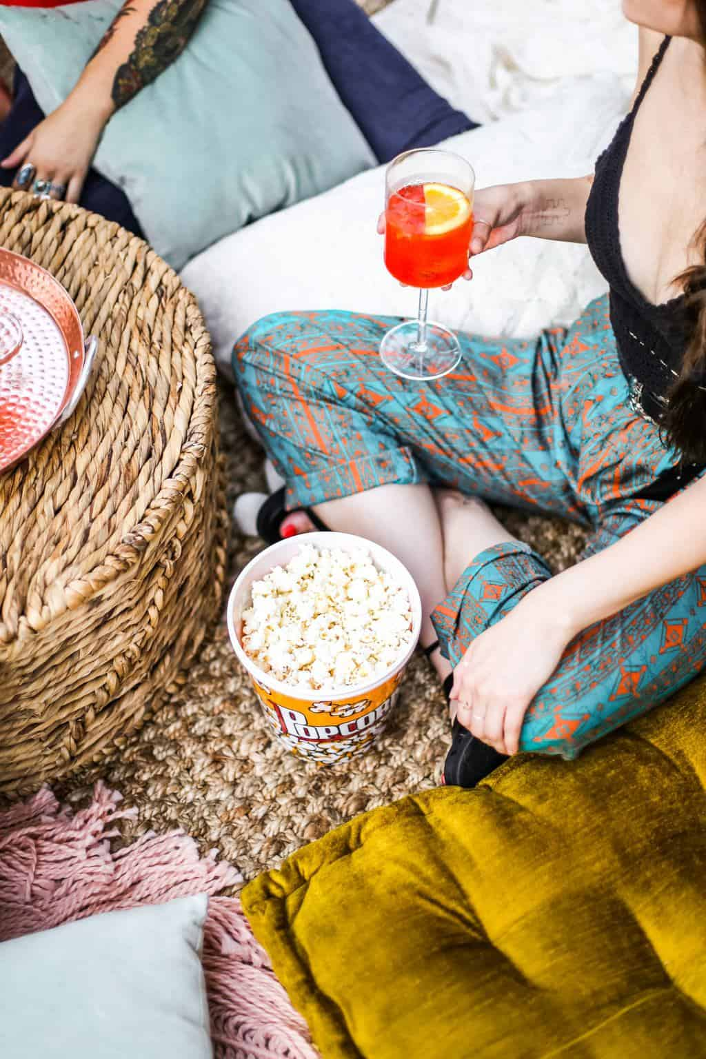 A girl with blue pants drinking an aperol spritz drink and eating a bowl of popcorn.