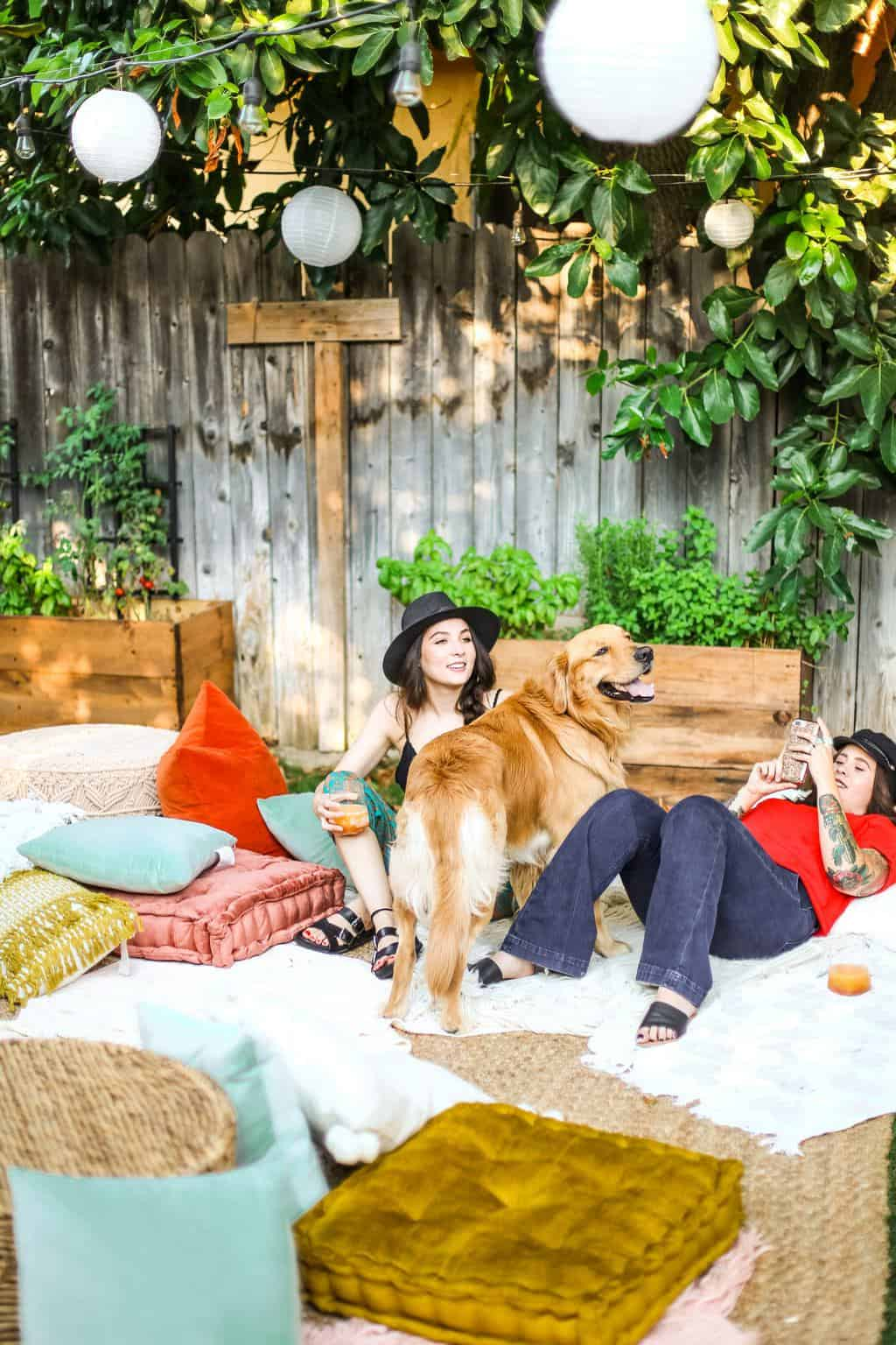 Two girls in a lounge area with a golden retriever at an outdoor movie night party.