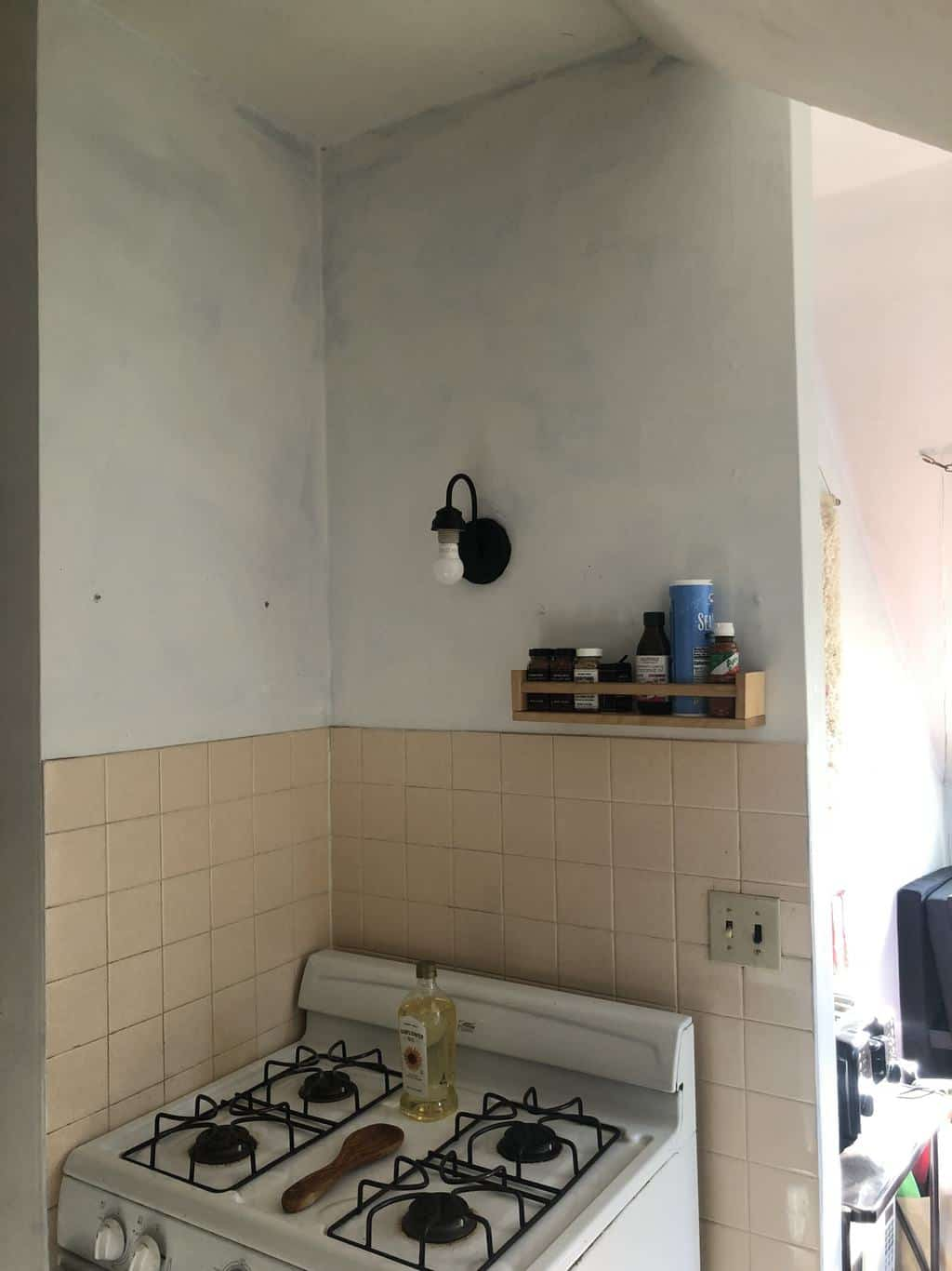 Before photo with white stove with and poorly painted walls.