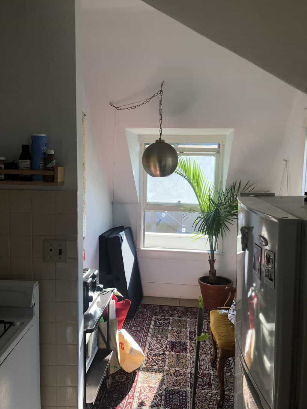 Small dinning room with no table and old light fixture.