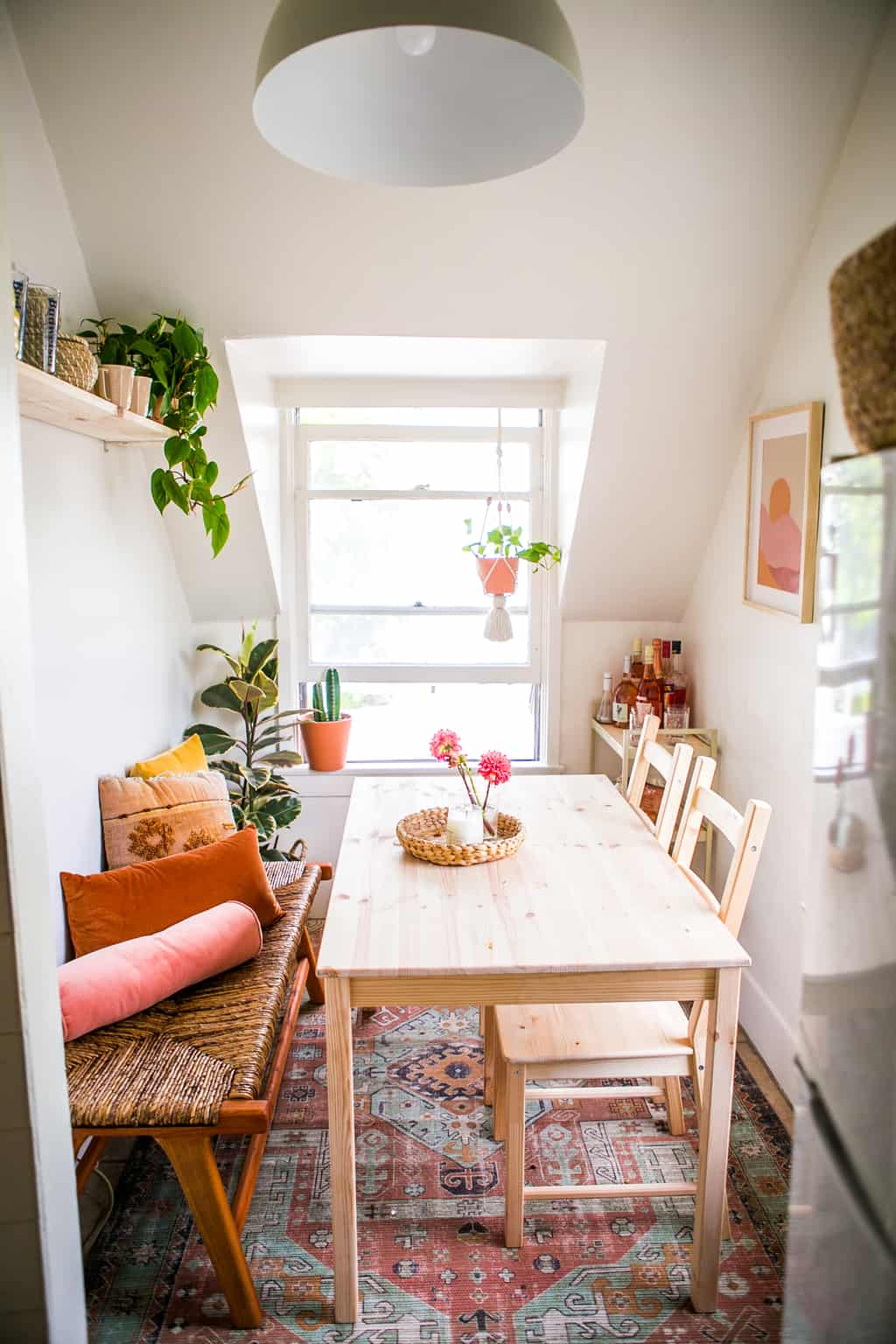 Small dinning room with a wooden table and bench with a rug and bar cart.