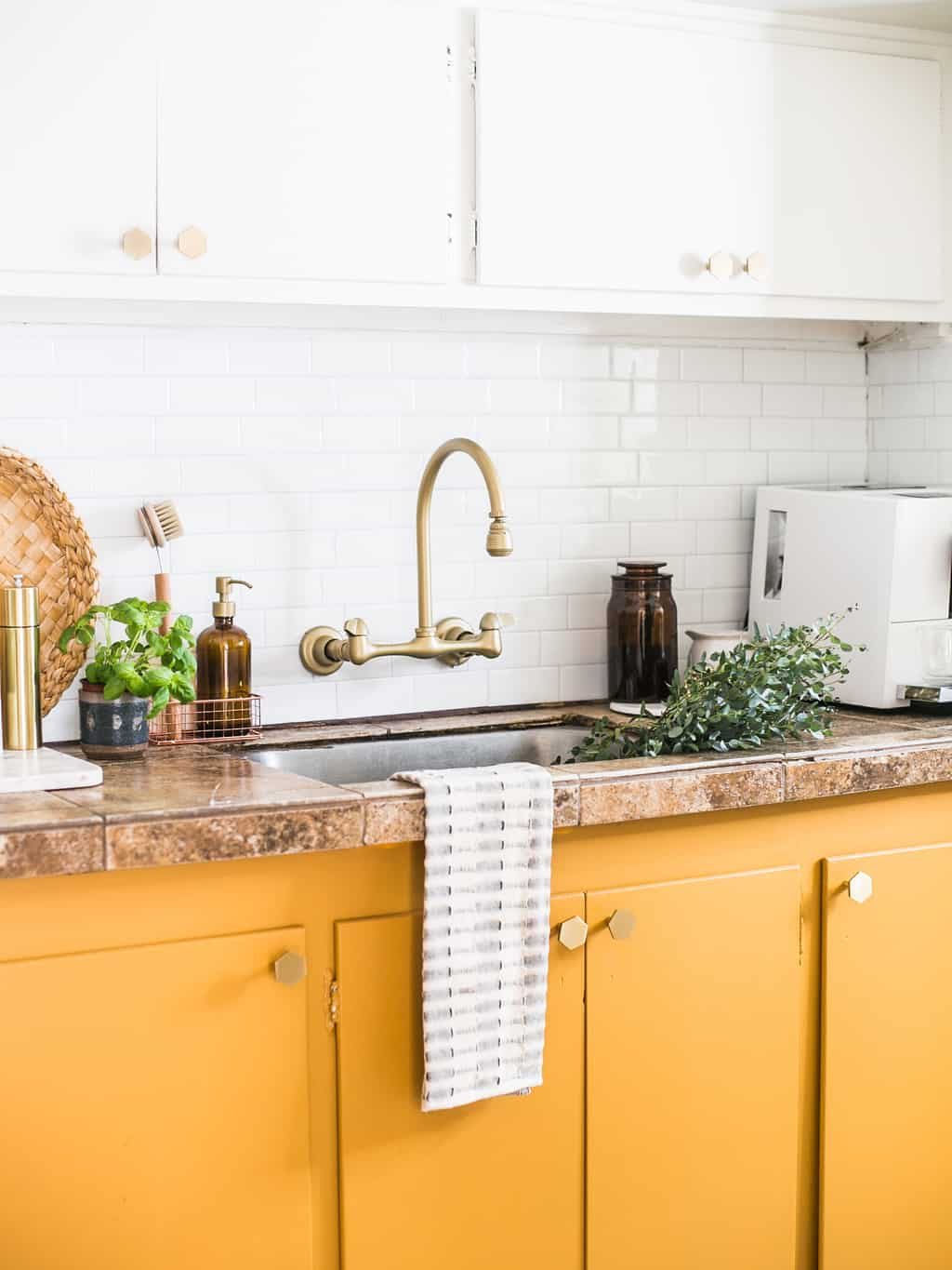 Mustard yellow cabinets with gold hardware.